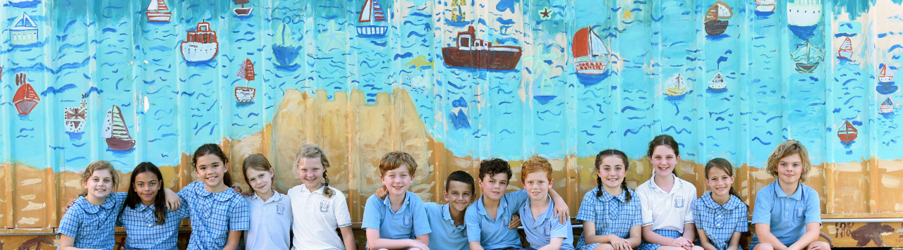 Balgowlah Heights with 13 students sitting in front of Mural